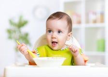 Glückliches Babykind, das Lebensmittel selbst mit Löffel isst Lizenzfreies Stockfoto
