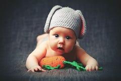 Glückliches Babykind im Kostüm ein Kaninchenhäschen mit Karotte auf einem Grau Stockfotografie
