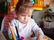 Glückliches Babykind zeichnet mit farbigen Bleistiftzeichenstiften Stockfotografie