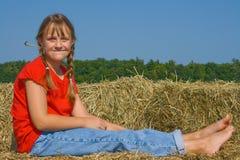 Glückliches Bauernhofmädchen mit einem Stück Stroh in ihrem Mund Stockfotos