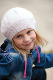 Glückliches blond-haariges Mädchen in einem weißen Hut mit den breiten Augen öffnen sich Stockfotografie
