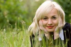 Glückliches blondes Baumuster über dem grünen Gras Stockbild