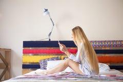 Glückliches blondes, ein Foto von mit ihrem Handy machend Stockfoto