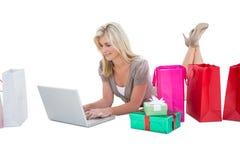Glückliches blondes Einkaufen online mit Laptop Lizenzfreie Stockfotos