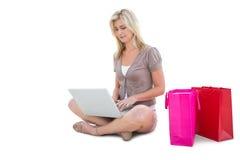 Glückliches blondes Einkaufen online mit Laptop Stockfotografie