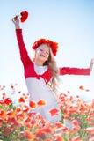 Glückliches blondes Feld des Kindermädchens im Frühjahr mit Mohnblumen Stockbild