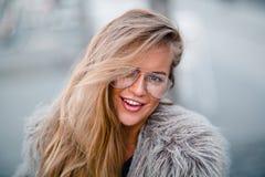 Glückliches blondes hübsches Mädchen im Mantel und Gläser schließen herauf Porträt Stockfotos