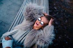 Glückliches blondes hübsches Mädchen im Mantel und Gläser schließen herauf Porträt Lizenzfreie Stockfotografie