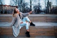 Glückliches blondes hübsches Mädchen im Mantel und Gläser schließen herauf Porträt Stockbilder