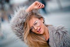 Glückliches blondes hübsches Mädchen im Mantel und Gläser schließen herauf Porträt Lizenzfreie Stockfotos