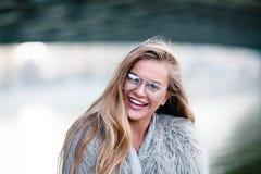 Glückliches blondes hübsches Mädchen im Mantel und Gläser schließen herauf Porträt Lizenzfreies Stockbild