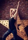 Glückliches blondes junges dünnes Frauentanzen im Blau zerriss Jeans auf yel Lizenzfreie Stockfotos