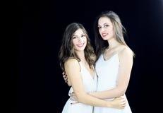 Glückliches blondes junges Mädchen zwei in der weißen Kleiderumfassung Lizenzfreie Stockfotografie