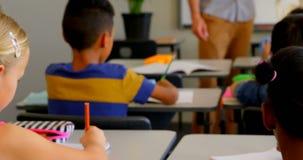 Gl?ckliches blondes kaukasisches Schulm?dchen, das in der Schule am Schreibtisch im Klassenzimmer 4k studiert stock video