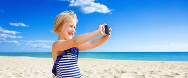 Glückliches blondes Kind auf der Seeküste, die Foto mit Digitalkamera macht Stockfotos
