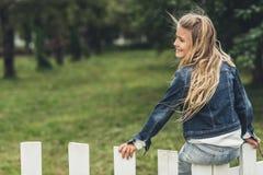 glückliches blondes Kind, das auf Zaun sitzt Lizenzfreie Stockbilder