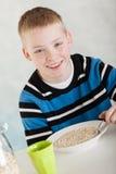 Glückliches blondes Kind, das Hafermehl in der Schüssel auf Tabelle isst Lizenzfreie Stockfotos