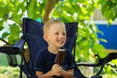 Glückliches blondes Kind, das Schokoladeneisriegel isst Lizenzfreie Stockbilder