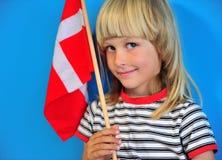 Glückliches blondes Kind mit einer Flagge von Dänemark stockfoto