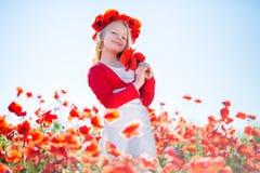 Glückliches blondes Kindermädchen auf dem Mohnblumengebiet Stockbilder