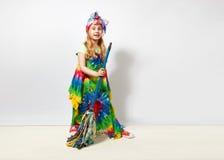 Glückliches blondes Kindermädchen im bunten Kleid der Hippie gegen weiße Wand Lizenzfreies Stockbild