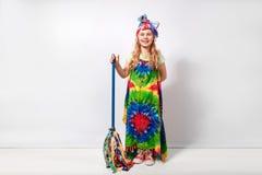 Glückliches blondes Kindermädchen im bunten Kleid der Hippie gegen weiße Wand Lizenzfreies Stockfoto