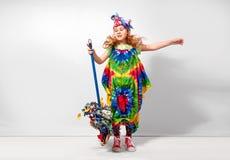 Glückliches blondes Kindermädchen im bunten Kleid der Hippie gegen weiße Wand Stockbilder