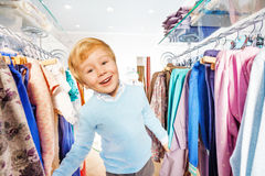 Glückliches blondes kleines Kind steht zwischen Aufhängern Stockbilder