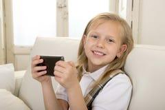 Glückliches blondes kleines Mädchen auf Hauptsofa unter Verwendung Internet-APP am Handy Stockfotos