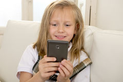 Glückliches blondes kleines Mädchen auf Hauptsofa unter Verwendung Internet-APP am Handy Lizenzfreies Stockbild