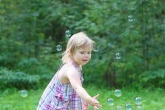 Glückliches blondes kleines Mädchen fängt Seifenblasen Stockfotos