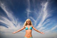 Glückliches blondes lächelndes Mädchen und das blaue helle Meer Lizenzfreie Stockfotos