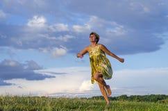 Glückliches blondes Mädchen, das barfuß auf Gras im Park auf dem grünen Gras auf einem bewölkten Himmel des Hintergrundes läuft Stockbild