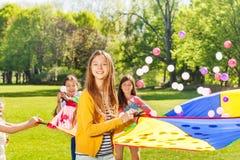 Glückliches blondes Mädchen, das draußen aktives Spiel spielt Stockfotografie