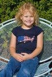 Glückliches blondes Mädchen, das in einem Gartenstuhl sitzt. Stockbilder
