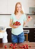 Glückliches blondes Mädchen, das Haufen von Erdbeeren hält Stockfotos