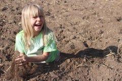 Glückliches blondes Mädchen, das im Schmutz spielt Stockbild