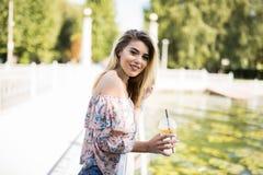 Glückliches blondes Mädchen, das am Park, eine Flasche von kaltem Juice While Smiling Into der Abstand trinkend sitzt Stockfotografie