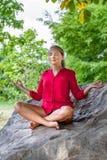 Glückliches blondes Mädchen, das unter einem Baum auf einem Stein meditiert Stockbilder
