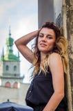 Glückliches blondes Mädchen der Junge recht mit dem langen Haar, das an der alten ruinierten Festungssteinwand, sonniger Tag des  Lizenzfreie Stockfotografie
