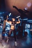 Glückliches blondes Mädchen der sexy Eignung in der Sportabnutzung mit perfektem Körper in der aufwerfenden und lächelnden Turnha Stockfotos
