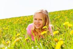 Glückliches blondes Mädchen in der Wiese mit Blumen Stockbild