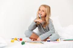 Glückliches blondes Mädchen mit Bleistift in ihrem Mund, der im Bett, looki sitzt Lizenzfreie Stockfotos