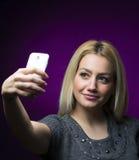 Glückliches blondes Mädchen mit dem langen Haar, das selfie nimmt Studioporträt auf purpurrotem Hintergrund Lizenzfreies Stockfoto