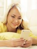 Glückliches blondes Mädchen mit einem Smartphone zu Hause Stockfotos