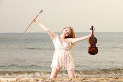 Glückliches blondes Mädchen mit einer Violine im Freien Stockbild