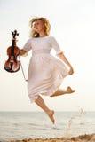 Glückliches blondes Mädchen mit einer Violine im Freien Stockfoto
