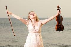 Glückliches blondes Mädchen mit einer Violine im Freien Stockbilder
