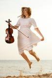 Glückliches blondes Mädchen mit einer Violine im Freien Stockfotos