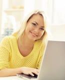 Glückliches blondes Mädchen mit Notizbuch zu Hause On-line-Einkaufen, Laptop Stockfotos